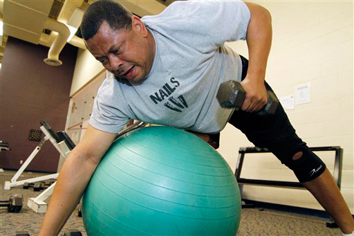 In this photo taken March 10, 2010, Sen. Eric Powell, D-Corinth, grunts as he lifts weights while trying to balance on a exercise ball during a predawn workout at Millsaps College with about 100 other legislators and staff members from various governmental offices. (AP Photo/Rogelio V. Solis)