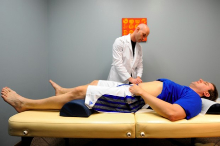 Acupuncturist and practitioner of Chinese medicine Craig Singer works on patient Chris Grygiel during a therapy session. (Photograph by Kyle Telechan/The Times.)