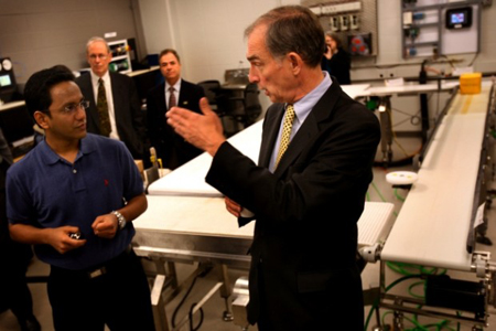 Purdue University Calumet School of Technology graduate student Gautam Agarwal, left, gives a brief overview of the university's new mechatronics laboratory to U.S. Rep. Pete Visclosky, D-Ind. (Photograph by Natalie Battaglia/The Times.)