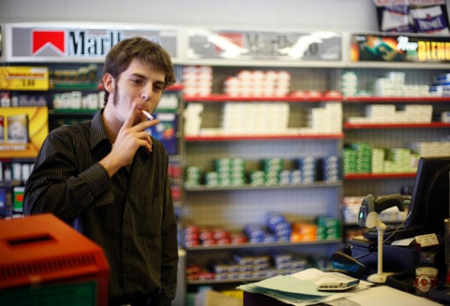 Tom Gardner, an employee at Cigarette Discount Outlet, smokes a cigarette behind the counter Friday at the Highland store. More than a quarter of adults smoke in Indiana, and state Rep. Charlie Brown, D-Gary, is planning to introduce legislation to ban smoking in all indoor public places, except casinos. (Photograph by Heather Eidson/The Times.)
