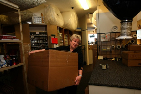 Employee Cindy Swanson, of Lansing, takes a customer's box full of holiday gifts destined for California to the back of the UPS store in Porte de'Leau Shopping Center in Highland. (Photograph by Natalie Battaglia/The Times.)