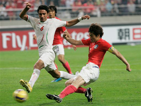 In this June 17, 2009 file photo, South Korea's Park Ji-sung, right, scores the first goal as Iran's Nekounam Javad looks on during their 2010 FIFA World Cup Asia group 2 qualifying soccer match at Seoul World Cup Stadium in Seoul, South Korea. ESPN, owned by the Walt Disney Co., on Tuesday, Jan. 5, 2010 said it will introduce a sports channel this year that will broadcast live sports events using 3-D technology, starting with the FIFA World Cup soccer match on June 11. (AP Photo/Ahn Young-joon, File)