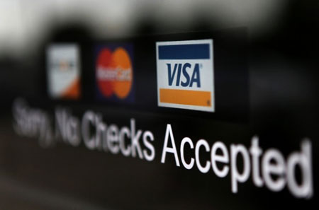A Visa sticker is shown at a business in Detroit. The new credit card regulations began Monday. Banks now need to abide a spate of new rules on terms and disclosures. The idea behind the landmark law was to prevent banks from using unfair practices that dig borrowers deeper into debt. (AP File Photo)
