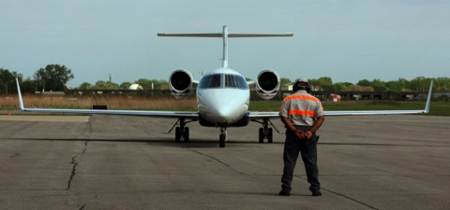 Lineman Dennis Montgomery prepares to flag out a Lear 45 business jet at the Gary Jet Center at the Gary/Chicago International Airport. (Photograph by John J. Watkins.)