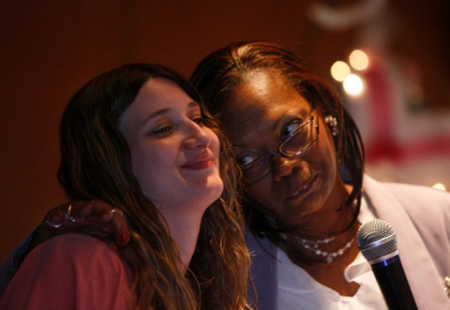 Maria, left, a resident at the ARC shelter, and Renitta Stout, executive cirector of the shelter, share a moment during the Majestic Star casino's annual Mother's Day reception honoring women from two local shelters. Casino employees donated thousands of dollars in clothing, toys, and various items to several local shelters. (Photograph by John Luke/The Times.)