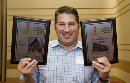 Franklin House co-owner Jason Evans holds up his Heritage Award, left, for historic preservation of a building in Valparaiso and his Community Improvement Award, right, after being honored at the 43rd annual Valparaiso Community Improvement Award luncheon at the Valparaiso University Harre Union Wednesday. (Photograph by The Times.)