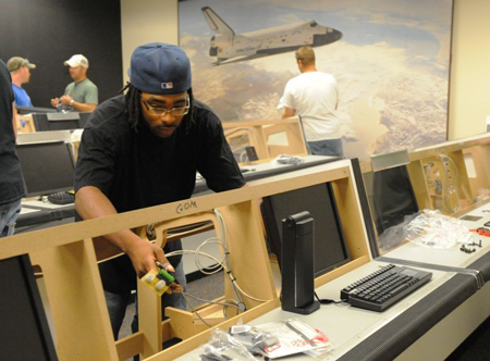 Anthony Hunter, a two-year apprentice in an Indiana-Kentucky Regional Council of Carpenters program, works Tuesday in the mission control room at the Challenger Learning Center in Hammond. Apprentice workers are donating hours of work installing items at the center located on the Purdue University Calumet campus. (Photograph by The Times.)