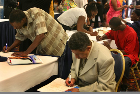Job seekers fill out applications on Sept. 1 at the Genesis Convention Center during the second annual Community Stimulus Career Fair hosted by the Gary Employment Resource Center. Nearly 50 businesses and educational institutions collected resumes and spoke to hundreds of applicants in search of employment and job training. (Photograph by The Times.)
