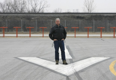 Wil Davis, Gary Jet Center owner, stands in 2008 at the northwest end of Gary/Chicago International Airport's main runway, just a few hundred feet from the railroad tracks that block its expansion. On Thursday, Davis warned the airport authority board that his business and others are in peril if the tracks are not moved. (Photograph by The Times.)