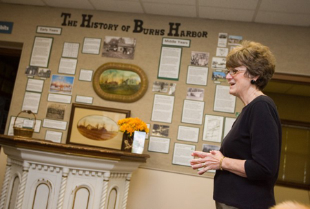 Westchester Township History Museum curator Jane Walsh-Brown talks last week about the Burns Harbor Exhibit, which traces the history of Westchester Township's youngest town from its early 19th century settlement through the years when it was known as Westport. Through various artifacts and photographs, the exhibit also looks at the construction of Bethlehem Steel, the town's incorporation and its present-day life. The exhibit is open through mid-January. (Photograph by The Times.)