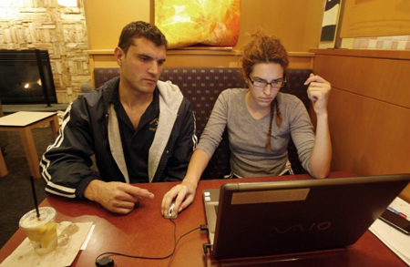 Marko Teovski and Endzi Stojanovska, both of Crown Point, browse the Internet using Wi-Fi at the Panera Bread in Merrillville. Like the national chain, many locally-owned coffee shops and restaurants are luring customers with free wireless service. (Photograph by The Times.)