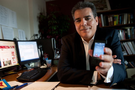 Tarik El-Naggar, chief operating officer at Get Vext, holds a cell phone on in his Crown Point office. The origins of GetVEXT came one year ago when a member of the Living Stones Fellowship congregation—where the business is partly based—thought it would be a good idea to be able to send a text message while driving without having to type. (Photograph by The Times.)
