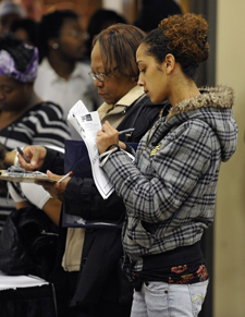 Unemployed workers fill out applications during a job fair sponsored by Scott Lee Cohen, Independent Candidate for Governor of Illinois, in Rockford, Ill. Applications for unemployment benefits fell last week for the fourth time in five weeks, a sign that layoffs are declining. (AP Photo/Jim Prisching)