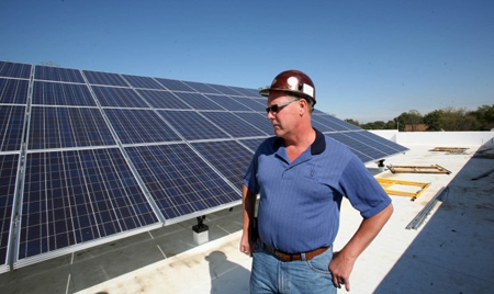 Raymond Kasmark, business manager for the International Brotherhood of Electrical Workers Local 697, stands near one of the solar panel assemblies on the roof of the union's new building in Merrillville. The facility is scheduled to be completed in December. (Photograph by The Times.)