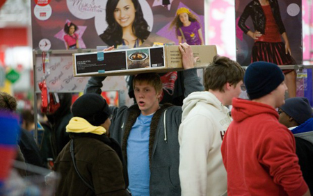 A shopper at the Hobart Target on U.S. 30 carries a box on his head just after 4 a.m. on Black Friday, November 26, 2010. Hundreds of deal seekers lined-up outside stores and battled freezing temperatures to purchase items at discount prices. (Photograph by Jon L. Hendricks/The Times.)