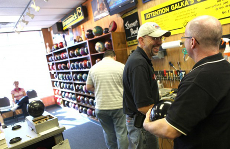 Wally Galka, second from right, owner of Galka's Pro Shop, laughs while working on bowling balls. The Dyer shop is celebrating 31 years in business. (Photograph by Heather Eidson/The Times.)