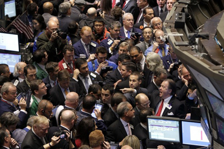 Traders gather near the post where General Motors Co. stock trades at the New York Stock Exchange on Thursday. (AP Photo/Seth Wenig)