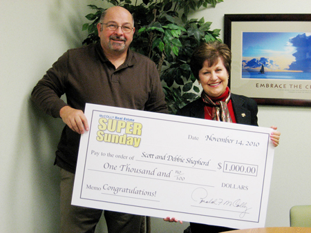 Scott Shepherd poses with the $1,000 check he won for the November Super Sunday Open House Event. Also pictured is McColly Real Estate Agent Lee Garafolo-Malizia. (Photograph courtesy of McColly Real Estate.)