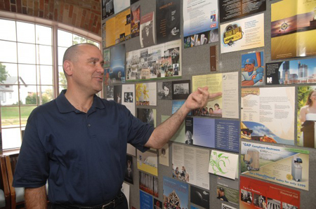 Kelly Newcomb, owner and president of Newcomb Solutions, shows some of the work that his Michigan City company has done for clients. (Photograph by The Times.)