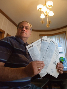 Jerry Armellino, of Valparaiso, holds up recent NIPSCO bills. He is disgusted by the 16.8 percent proposed NIPSCO electric rate hike for residential customers and has written to elected officials asking them to fight it. The increase is under appeal. (Photograph by The Times.)