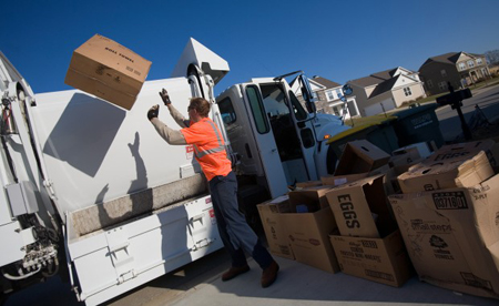Valparaiso public works employee Dan Brugos throws cardboard boxes into a recycling truck during his route Monday in the Hawthorne subdivision. (Photograph by The Times.)