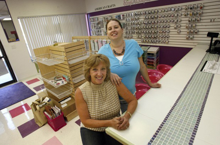 Pam Nachel, sitting, and her daughter, Jessica Altman, are owners of Stamp N Scrap Ink, a new scrapboook and stamping store that opened October 2 in Dyer. (Photograph by The Times.)