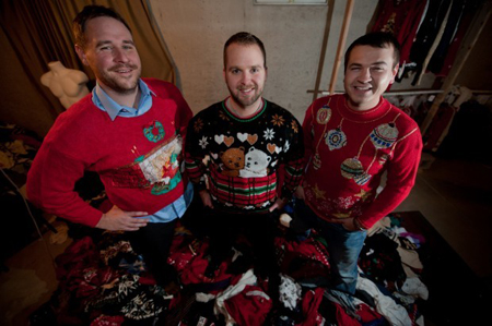 Kevin Wool, from left, Adam Paulson and Brian Miller, co-owners of UglyChristmasSweaterParty.com, stand on a pile of sweaters Wednesday in their St. John headquarters. The trio runs the website where users are able to order a variety of ugly Christmas sweaters. (Photograph by Kyle Telechan/The Times.)