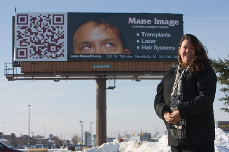 Leslie Robinson, owner of Mane Image, recently had a billboard installed on U.S. 30 in Hobart that uses a quick response code. Consumers can scan the 2-D image and be connected to a website, photo or video. The popularity of the 2-D technology is growing in the U.S. (Photograph by Jon L. Hendricks/The Times.)