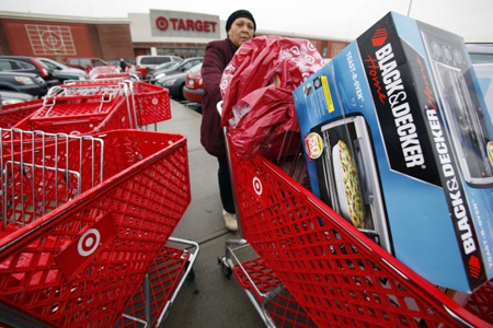 A shopper leaves a Target store in Boston. Discount retailer Target Corp. said Thursday more shoppers came to its stores in November and spent more than a year earlier, helping a key revenue figure rise 5.5 percent during the month, more than expected. (AP Photo/Michael Dwyer)