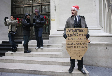 "Jesse Paloger holds up a sign while standing on Wall Street as he hopes to find a job, in New York. Paloger, who has an accounting and economics degree from the University of California, Santa Barbara, has written on the bottom of his sign, ""Go-getter from California looking for my shot!"" Fewer people applied for unemployment benefits during the first full week of December, the third drop in the past four weeks and a sign that the job market is slowly improving. (Photograph by Mark Lennihan/Associated Press.)"