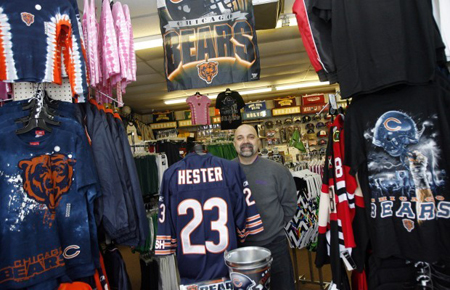 Tom Palinca, store manager at Magic Sports shows off some of the Chicago Bears apparel on display at the sports clothing store. The Bears will meet the Green Bay Packers on Sunday for the NFC championship. (Photograph by John Luke/The Times.)