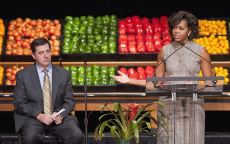 Wal-Mart President and CEO Bill Simon looks on as First lady Michelle Obama takes part in Wal-Mart's announcement of a comprehensive effort to provide healthier and more affordable food choices to their customers, Thursday in Washington. (Photograph by Cliff Owen/Associated Press.)