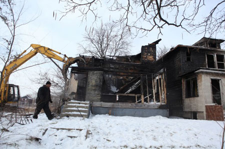 A crew demolishes an abandoned home on December 20, 2010, in Gary. U.S. Sen. Evan Bayh, D-Ind., helped secure funding for the work after touring the house last year with a U.S. Department of Housing and Urban Development official. (Photograph by Heather Eidson/The Times.)
