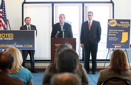 Local officials join Indiana Commerce Secretary Mitch Roob, right, during a news conference Monday at the Hammond marina to announce efforts to lure Illinois employers to Northwest Indiana. At the lectern is Mark Maassel, president and CEO of the NWI Forum, and to left is Don Babcock, economic development director for NIPSCO. (Photograph by Jonathan Miano/The Times .)