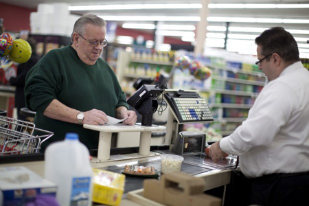 Ron Mize, left, buys groceries at the Strack &#038; Van Til grocery store in Lowell. David Wilkinson, Strack &#038; Van Til president and CEO, said the company is investing more than $2 million in the Lowell store. (Photograph by Kristin Elkins/The Times.)
