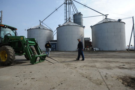 Bobby Hayden, left, and Tom Vandercar walk to the grain bins to unload corn into a trailer for market while getting ready for the spring season at the Hayden family farm in Hebron. (Photograph by Gregg Gearhart | The Times)